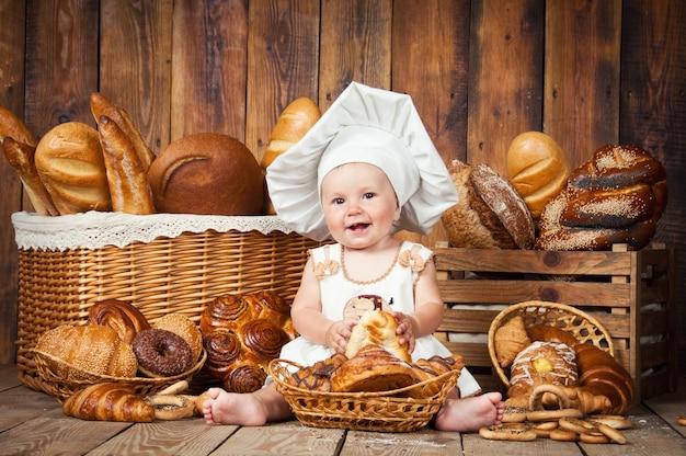 Niño pequeño con gorro de cocinero y productos de panadería.