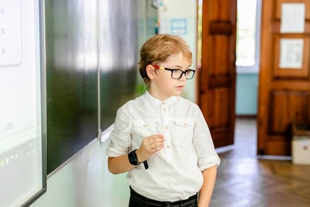 Niño pequeño con grandes gafas negras y camisa blanca de pie cerca de la pizarra de la escuela con un trozo de tiza haciendo cara de pensamiento inteligente