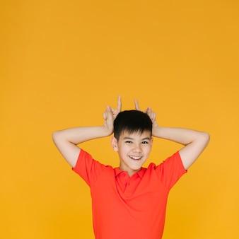 Niño pequeño haciendo cuernos con sus dedos
