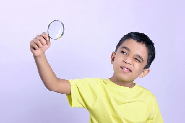 Niño pequeño indio viendo magnificar