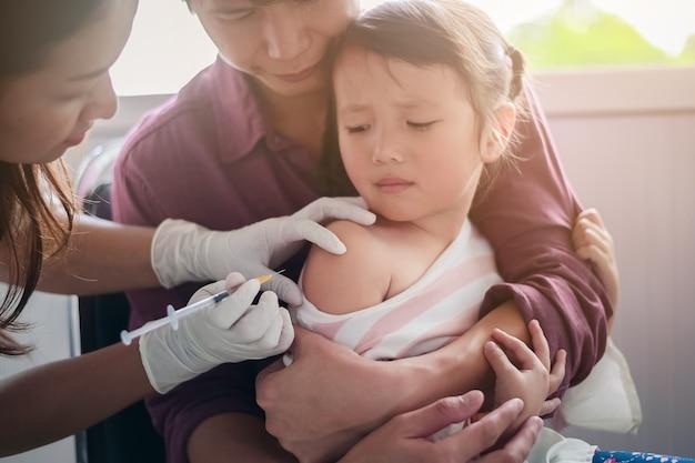 Niño pequeño con inyección, médico de primer plano inyectando la vacuna en el brazo de una niña asiática, con el padre abrazando al niño, por no retorcerse mientras se inyecta la vacuna