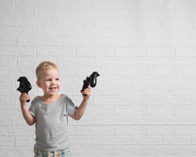 Niño pequeño con joystick en manos espacio de copia