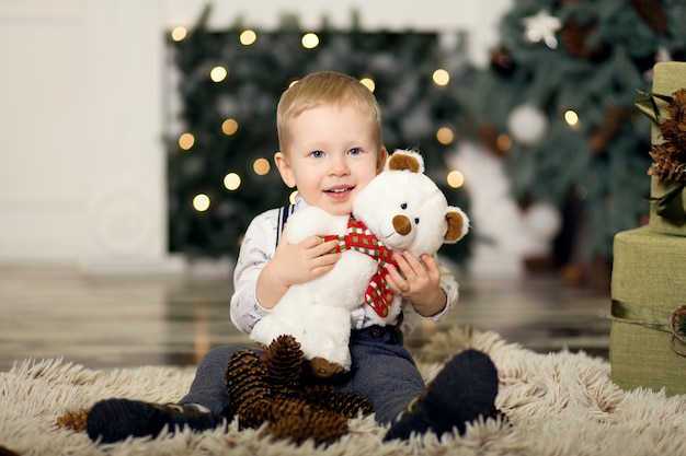 Niño pequeño juega con el oso de peluche cerca de un árbol de navidad.