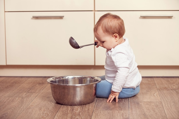Un niño pequeño juega en el piso de la cocina.