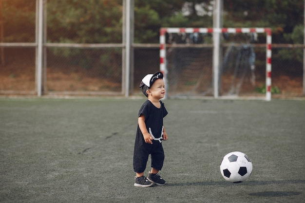 Niño pequeño jugando al fútbol en un campo de deportes