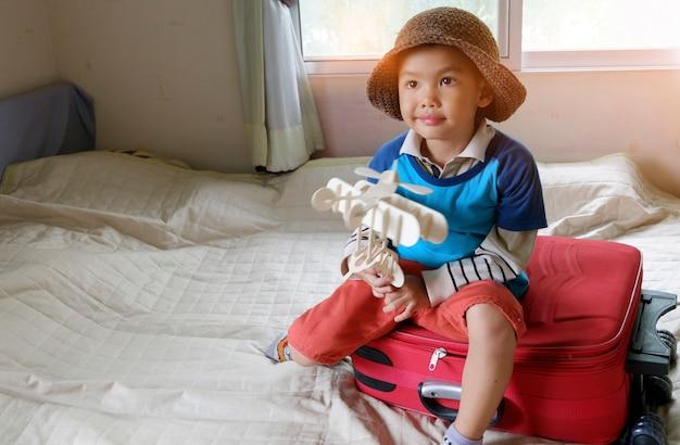 Niño pequeño jugando con avión de juguete, viaje y concepto de aventura