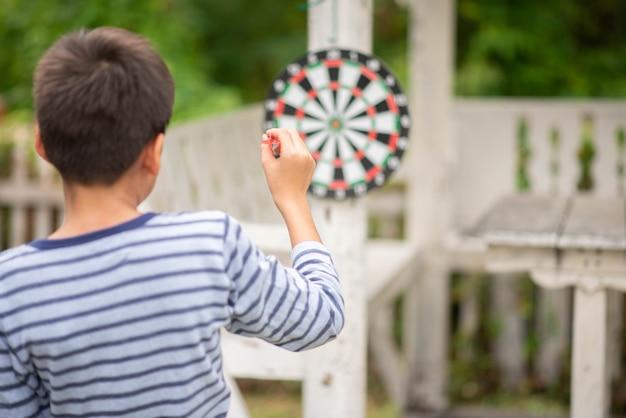 Niño pequeño jugando dardos junta actividad familiar al aire libre