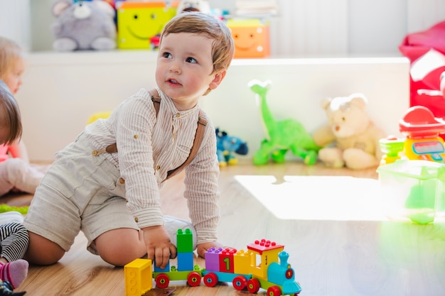 Niño pequeño jugando con el juguete del tren