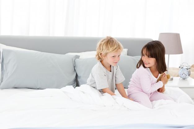 Niño pequeño jugando con su hermana en la cama de sus padres