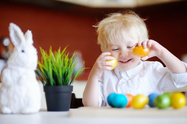 Niño pequeño lindo cazando huevos de pascua el día de pascua