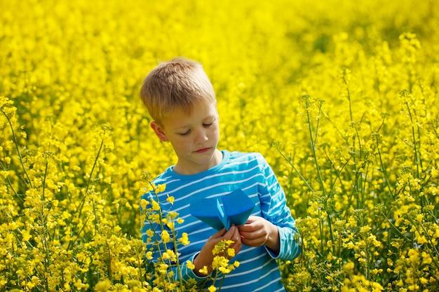 Niño pequeño lindo y feliz que juega con el aeroplano de papel en día soleado