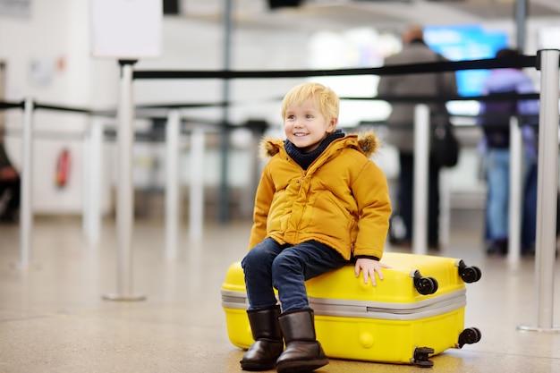 Niño pequeño lindo con la maleta amarilla grande en el aeropuerto internacional antes del vuelo