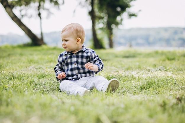 Niño pequeño lindo niño sentado en el césped en el parque