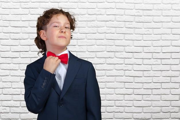 Niño pequeño lindo que ajusta su corbata de lazo