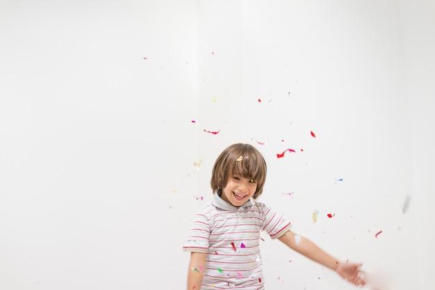 Niño pequeño lindo que celebra para la fiesta en el espacio blanco de la copia de la pared