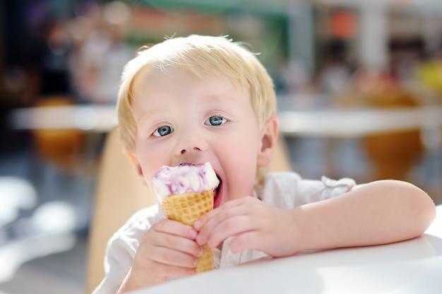 Niño pequeño lindo que come el helado de helado en italiano en el interior del café. dulces / azucareros para niños pequeños.