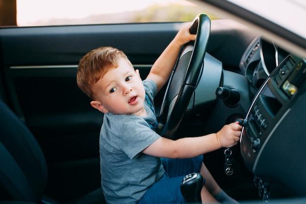 Niño pequeño lindo que conduce el coche de padres
