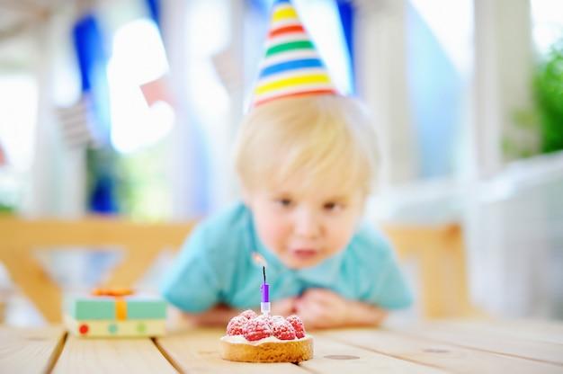 El niño pequeño lindo que se divierte y celebra la fiesta de cumpleaños con la decoración y la torta coloridas