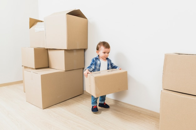 Niño pequeño lindo que lleva las cajas de cartón en el nuevo hogar