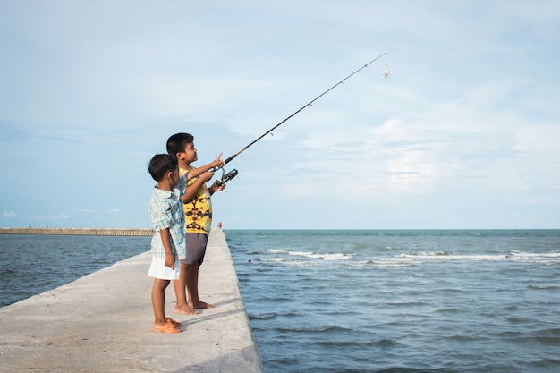Niño pequeño lindo que pesca en el mar
