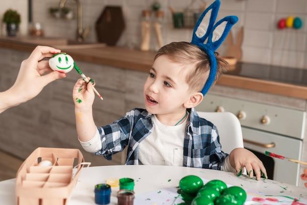 Niño pequeño lindo que pinta los huevos de pascua