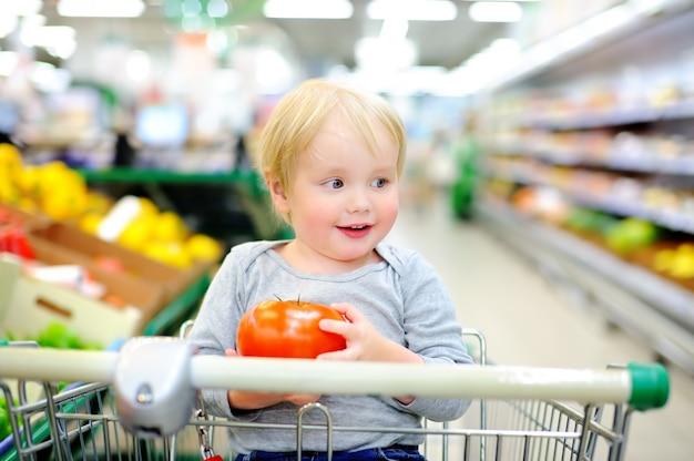 Niño pequeño lindo que se sienta en el carro de compras en una tienda de alimentos o un supermercado
