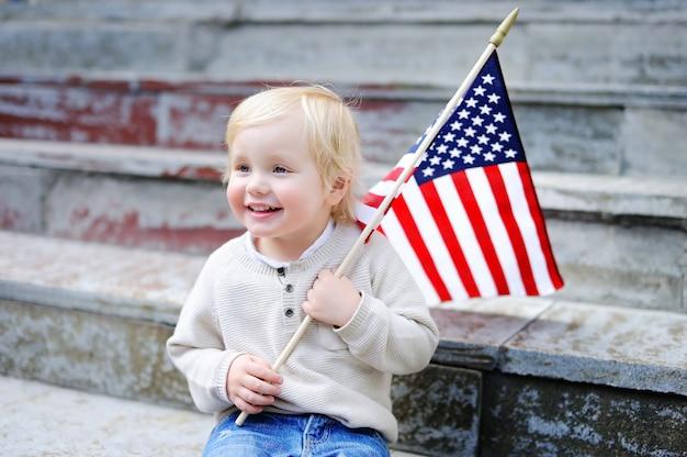 Niño pequeño lindo que sostiene la bandera americana. concepto de día de la independencia.