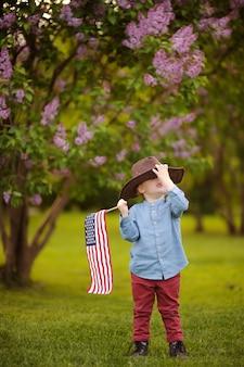 Niño pequeño lindo que sostiene la bandera americana en parque hermoso.