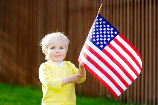 Niño pequeño lindo que sostiene la bandera americana.
