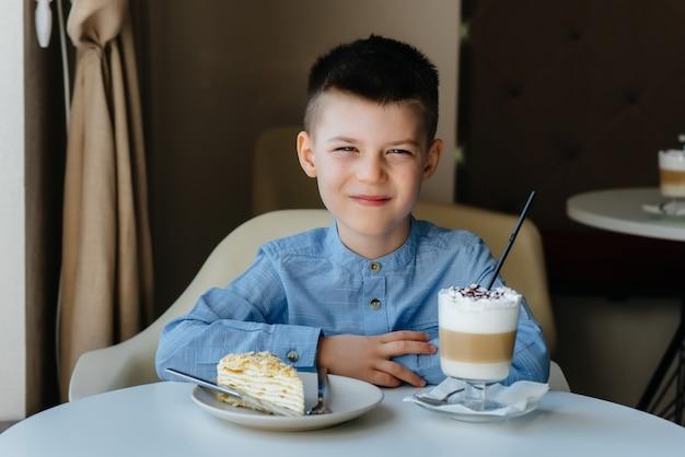 Un niño pequeño lindo está sentado en un café y mirando un pastel y primer plano de cacao. dieta y nutrición adecuada.