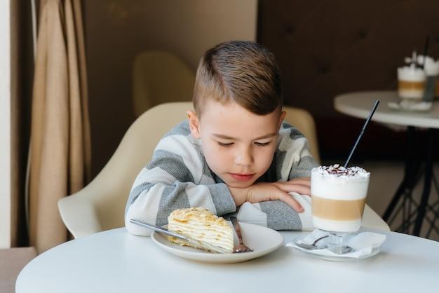 Un niño pequeño lindo está sentado en un café y mirando un pastel y primer plano de cacao.