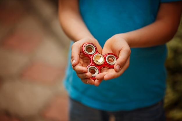 El niño pequeño lindo sostiene una persona agitada del hilandero en sus manos. juguete de moda y popular para niños y adultos.