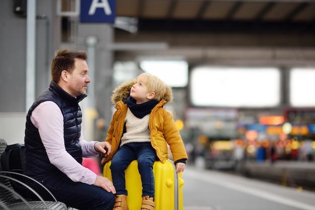 Niño pequeño lindo y su padre esperando tren expreso en la plataforma de la estación de ferrocarril
