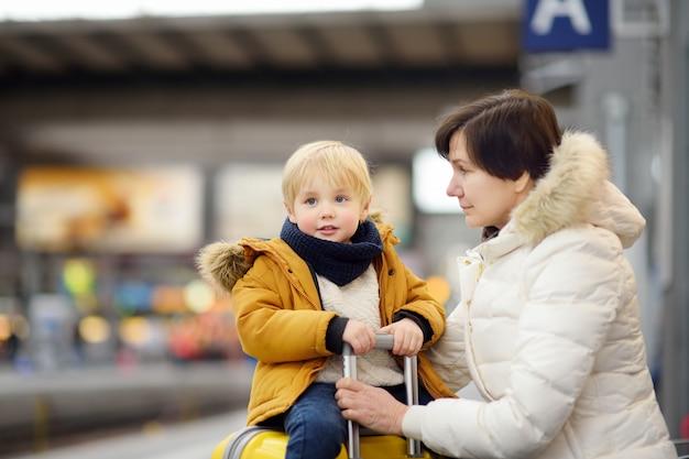 Niño pequeño lindo y su tren expreso que espera de la abuela / de la madre en la plataforma de la estación de ferrocarril