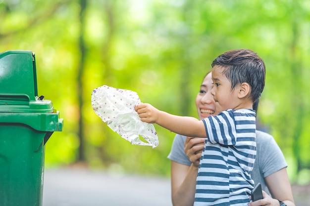 El niño pequeño lindo está vaciando basura en una papelera de reciclaje