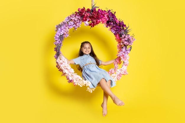 Un niño pequeño lindo vista frontal en vestido azul smilign y sentado en el columpio de flores