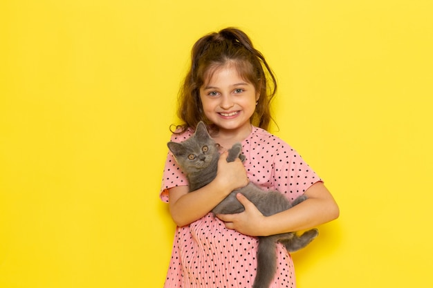 Un niño pequeño lindo de la vista frontal en vestido rosa que sostiene el gatito gris y que sonríe