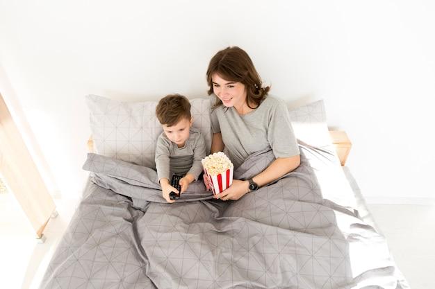 Niño pequeño con mamá acostada en la cama