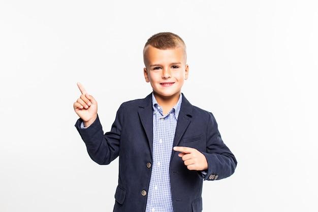 Niño pequeño con la mano vacía levantada señalando, aislado en la pared blanca