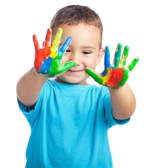 Niño pequeño con las manos con pintura
