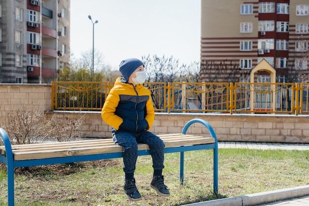 Un niño pequeño con una máscara camina en el patio de juegos durante la cuarentena. quédate en casa.