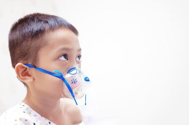 Niño pequeño con máscara de inhalador en el hospital