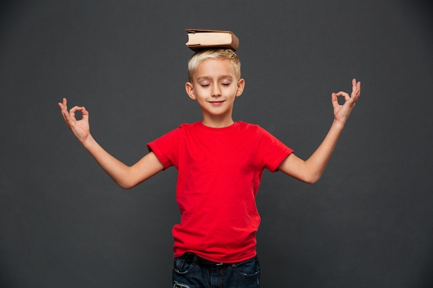 El niño pequeño medita con el libro en la cabeza.