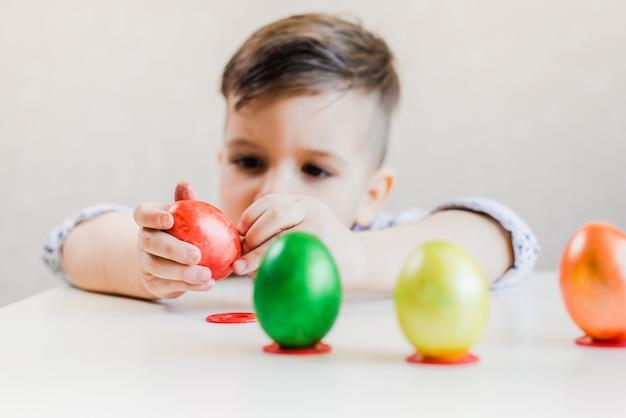 Un niño pequeño en una mesa blanca sostiene en sus manos y pela un huevo de pascua rojo sobre un fondo blanco.