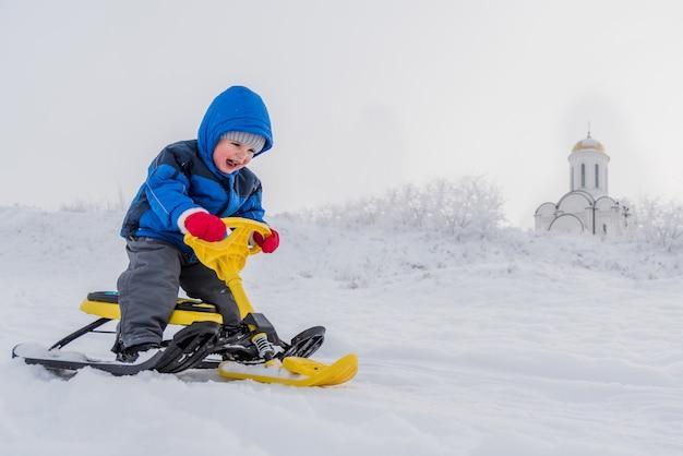 Niño pequeño montando una moto de nieve en invierno