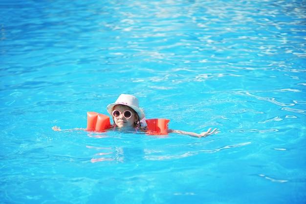 Niño pequeño nadando en la piscina