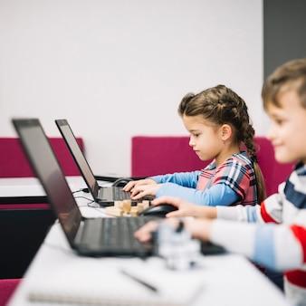 Niño pequeño y niña usando laptop en el aula