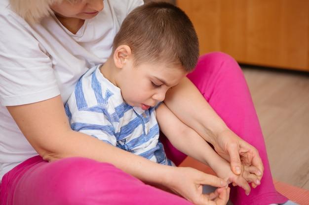Un niño pequeño con parálisis cerebral recibe terapia musculoesquelética haciendo ejercicios de fijación corporal