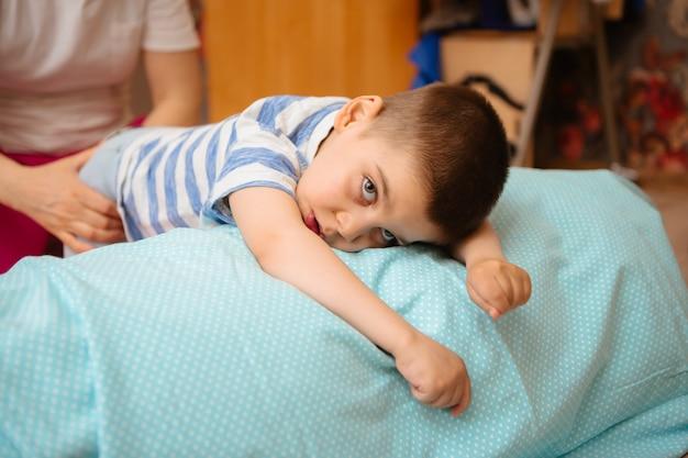 El niño pequeño con parálisis cerebral recibe terapia musculoesquelética haciendo ejercicios