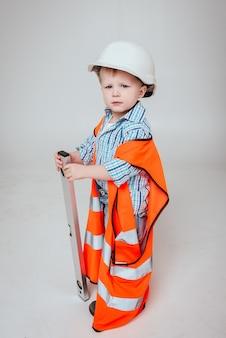 Niño pequeño en la pared blanca. construcción